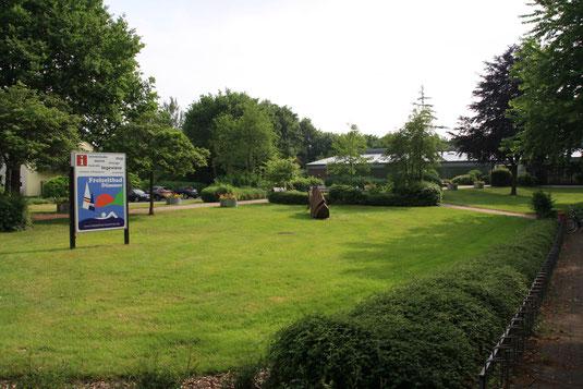 Auf dem grünen, von Büschen und Bäumen gesäumten Rasen ist das Schild des Hüder Hallenbads zu sehen.