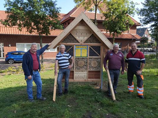Ein etwa 2,50 Meter hohes aus Holz gefertigtes Insektenhotel, gefüllt mit unterschiedlichem Material steht auf einer Wiese. Zu sehen sind vier Männer, die es dort aufgestellt haben.