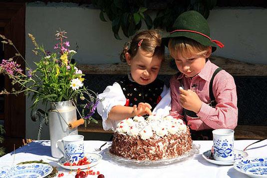 Zwei Schwarzwaldkinder essen eine Schwarzwälder Kirschtorte