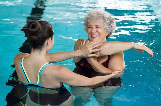 Physiotherapeutin mit Patientin beim Funktionstraining im Wasser