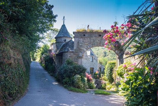 Ein typisches Manoir auf dem Cotentin mit Erkern und Torbogen und vielen Blumen.