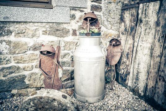 Musizierende Frösche hergestellt aus verrostetem Blech rund um eine Milchkanne in der Normandie