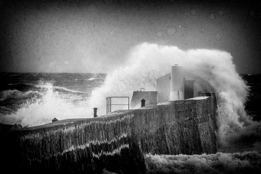 Eine Welle bricht sich über der Hafenmole in Carteret auf dem Cotentin.