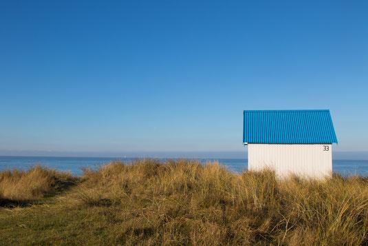 Eine Badekabine mit blauem Dach in den Dünen von Gouville in der Normandie