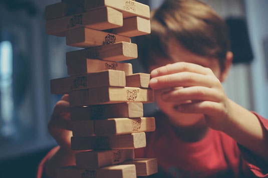 Confident young boy playing Jenga game.