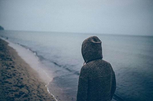 Depressed lonely man on beach.