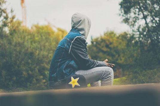 Depressed teenager in hoodie.