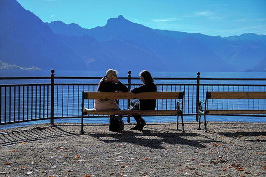OCD-free woman relaxing with friend by mountain lake.