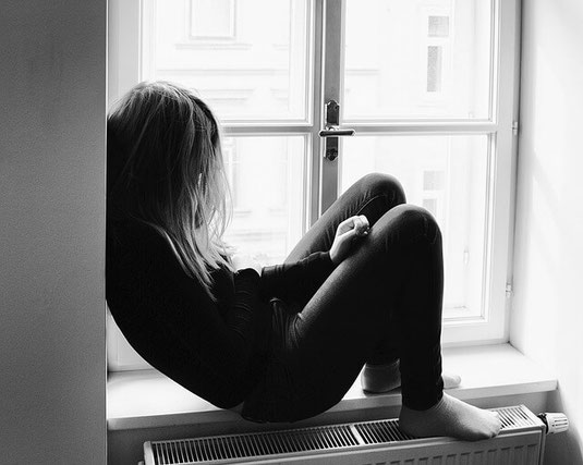 Depressed self-harming girl by window.