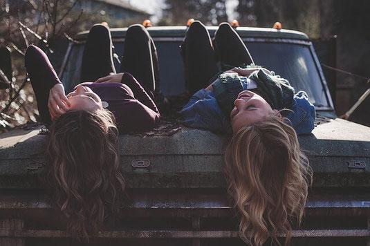 Two carefree teenage girls lying on car.