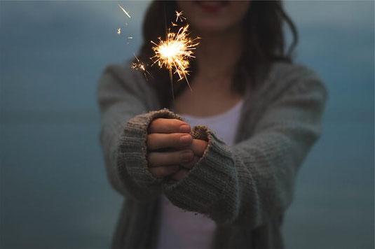Panic-free woman holding sparkler.