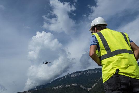 Le télé-pilote de drone est de dos, un gilet jaune et un casque de chantier pour la sécurité et la visibilité. Il pilote son drone qui, sur l'image, se détache de son arrière plan, un nuage très contrasté.