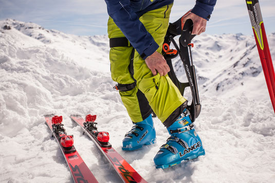 A man standing next to skis in ski boots puting on the againer ski system
