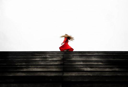 FRau in rotem Kleid geht einer besseren Zukunft entgegen