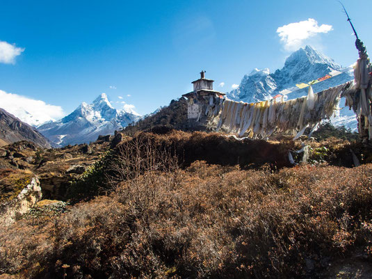 Eine kleine Stupa mit unzähligen Gebetsfahnen vor einer traumhaften Bergkulisse