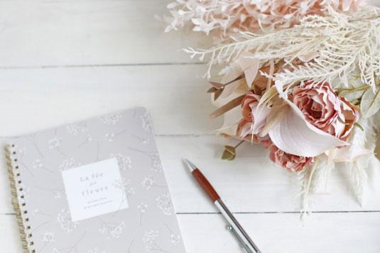 観葉植物が置かれたオフィス。ホワイトボード、テーブルに置かれたノートパソコン、タブレット、マグカップ。