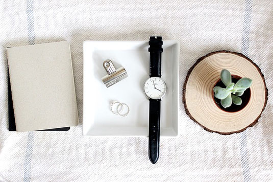 手帳。メモ。黒の革ベルトの腕時計。クリップ。指輪。卓上サイズの観葉植物。