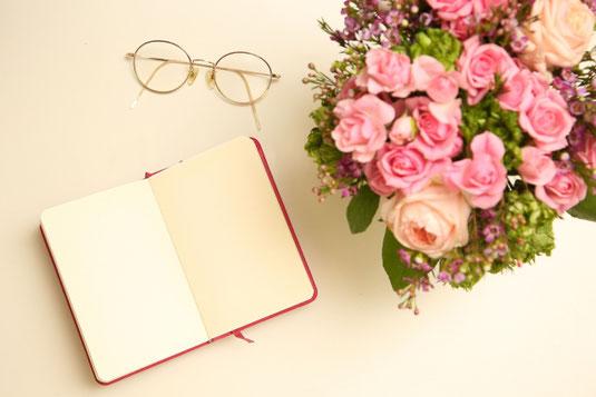 ノートの白紙のページ。ピンクのバラやケイトウの小さなブーケ。