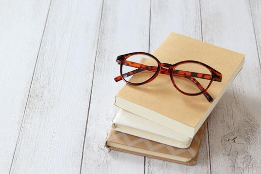 ハードカバーの本を目線上に持ち上げて読む女性。