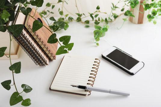 デスクに立てかけられた数冊のノート。広げられたノートと万年筆。傍らに置かれたスマートフォン。観葉植物のグリーンのつる。