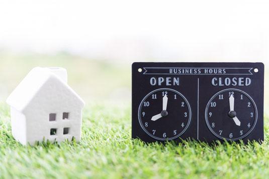 白のミニチュアハウスと置時計。始業時刻と終業時刻を指す2つの時計。