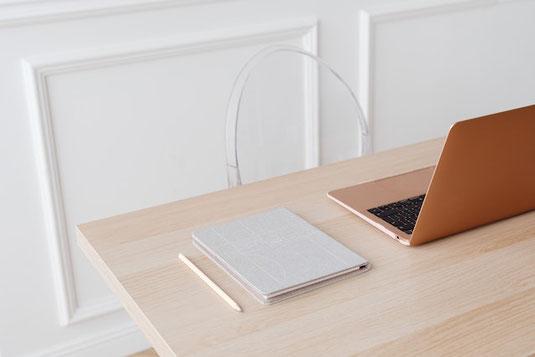 デスクに置かれたメモ帳と万年筆。書籍のうえに置かれた小さなブーケ。デスク一面に散らばった花びら。砂時計。