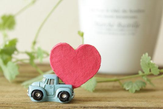 真心のハートを運ぶ車のクレイ模型がデスク上に載っている。その背面に観葉植物のグリーンが爽やかさを添えている。