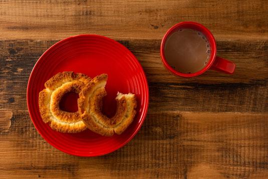 ドーナッツの載った赤のお皿。かじりかけのドーナッツ。ミルクコーヒーが入った赤のマグ。