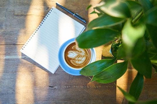 デスクの上の観葉植物を照らす太陽の光。傍らにノートとペン、コーヒーの入ったマグカップ。