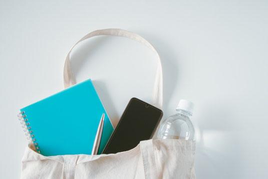 テーブルに広げられたノートパソコン、スマホ、電卓、ボールペン。淹れたてで湯気がたつコーヒー。
