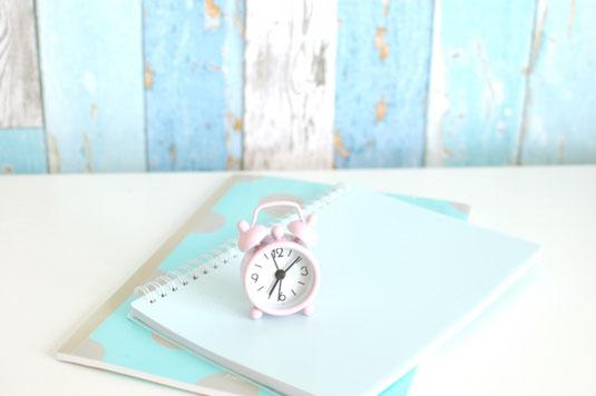木目調のデスクに広げられたノートパソコン、ノート、ペン、コーヒーの入ったマグカップ、ポプリの入ったガラスの瓶。
