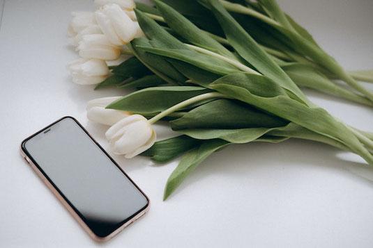 キャリーケースを引いて歩道を歩くビジネススーツ姿の女性。出張。