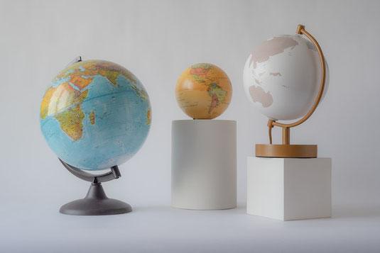 広げられた世界地図のうえに置かれたオートミールの皿。アーモンドで書かれたスマイル。