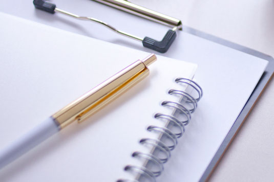 ピンクの表紙のノート、白紙のページが開かれたノート。ボールペン、眼鏡。