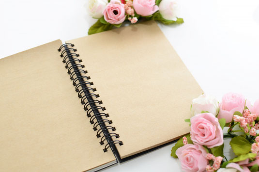 リングノートとピンクのバラのアレンジメント。