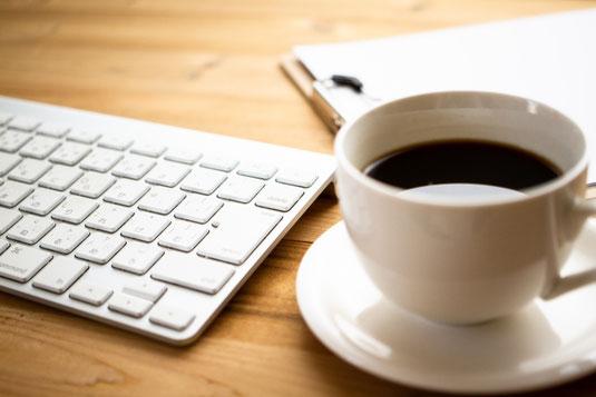 ノートパソコンのキーボードの上に置かれた手帳とスマホ。傍らにテイクアウトコーヒーと腕時計。卓上サイズの観葉植物。