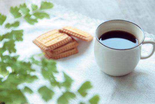 オフィスの打ち合わせテーブルに無造作に置かれたノートパソコン、メモ帳、ボールペン、コーヒーの入ったマグカップ。