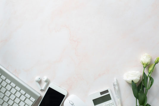 パソコンのキーボード。スマホとイヤホン。マウス。電卓とボールペン。白のバラ。