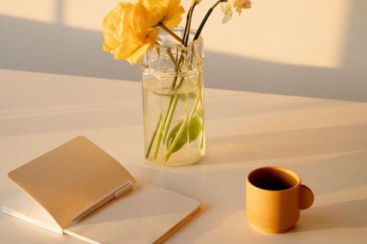 パソコンのキーボードの前に置かれたリングノートとボールペン。赤いリンゴ。白のガーベラ。ミモザの花。