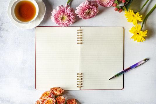 デスクに広げられた便箋と万年筆。傍らに積まれたノートと手帳。ひと房のブルーベリーの小枝。