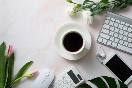 テーブルに無造作に置かれた白のバラとピンクのチューリップ。コーヒーの入った白のカップ&ソーサ。パソコンのキーボード。スマートフォン。マウス。電卓。イヤフォン。
