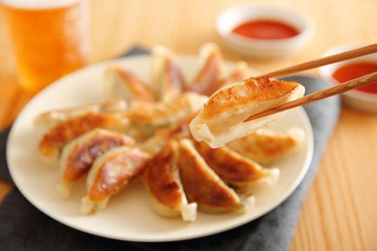 レモンを添えたハイボールのグラス。カッティングボードに並べられたピンチョスのおつまみ。