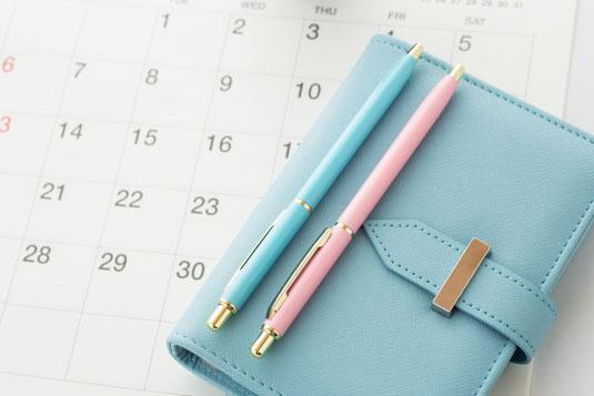 カレンダーの上に置かれた水色の手帳。ブルーとピンクのボールペン。