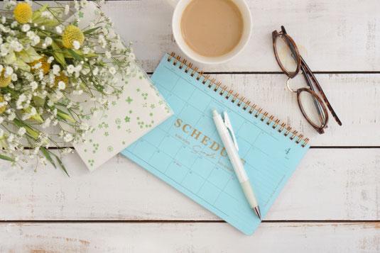 卓上カレンダーとボールペン、手帳。リーディンググラス。コーヒーのマグ。セファロフォラとカスミソウのブーケ。