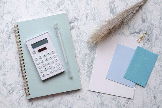 花びんの置かれたダイニングテーブル。棚の上に置かれた炊飯器、電子レンジ、トースター、ケトル。観葉植物の鉢植え。