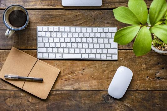 パソコンのキーボードのうえに置かれた白の腕時計。マウス。
