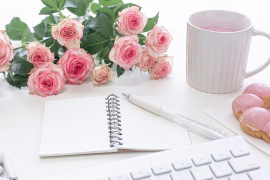 メモ帳とボールペン。パソコンのキーボードとイヤフォン。白のマグカップ。イチゴチョコのかかったドーナッツ。ピンクのバラの花束。