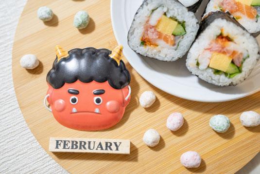 3月のカレンダー。黄色のガーベラとカスミソウ。レースのナプキンのうえに広げられたアソートクッキー。