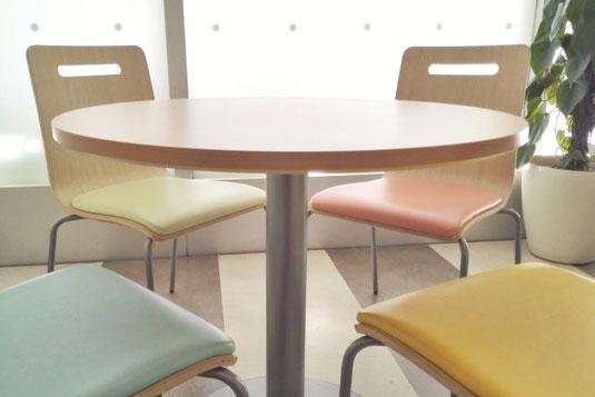 オフィスの打ち合わせスペース。丸テーブルといす。傍らに観葉植物。窓から陽が差し込んでいる。
