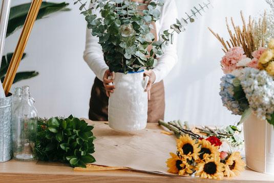 デスクに置かれた時計4つ。水色の目覚まし時計、赤のフレームの掛け時計、四角い掛け時計、ゴールドの丸い掛け時計。